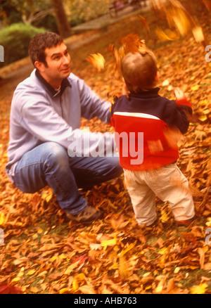 Vater mit seinem Sohn im Herbst draußen spielen - Stockfoto