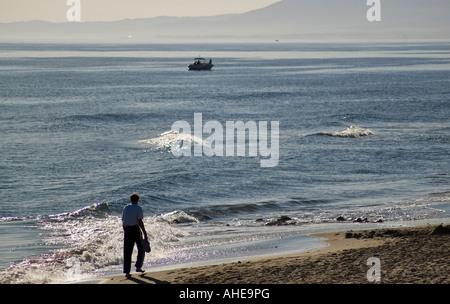 Mann, teilweise Silhouette zu Fuß auf einem spanischen Strand. - Stockfoto