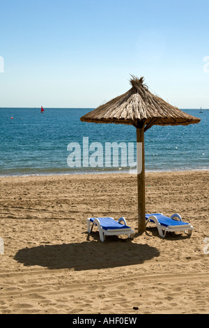 Zwei leere Liegestühle und Sonnenschirm am Strand von Swanage, Dorset, England - Stockfoto