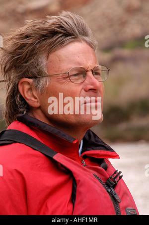 Mann trägt eine rote Schwimmweste und Brille suchen in in den Wind auf dem Colorado River im Grand-Canyon-Nationalpark, - Stockfoto