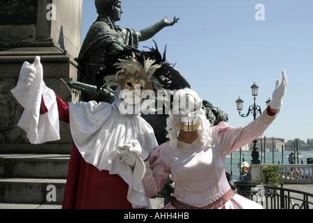Zwei menschliche Statuen in Venedig mit der realen Sache hinter. - Stockfoto
