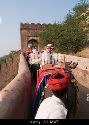Touristen in Richtung Tor zum Amber Fort hinter roten Turban der Mahout Elefanten reiten. Jaipur Indien - Stockfoto