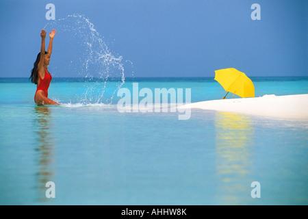 Frau allein im Paradies mit Sonnenschirm im seichten Wasser aus Sandbank - Stockfoto