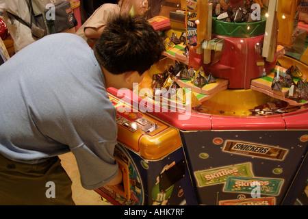 Übergewichtige junge in einer Maschine, die er Süßigkeiten bekommen gewonnen - Stockfoto
