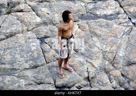 Klettergurt China : Nackter oberkörper bergsteiger auf einer steilküste mit klettergurt