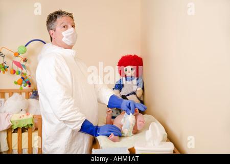 Vater im Dekontamination Anzug wechselnden Babywindel - Stockfoto