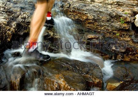 Mans Füße Fuß bis Dampf mit kleinem Wasserfall, Salomon Tech Amphibian Schuhe zum Wandern in Schluchten konzipierten - Stockfoto