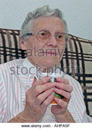 Ältere Frau tief in Gedanken halten Tasse Tee oder Kaffee UK - Stockfoto