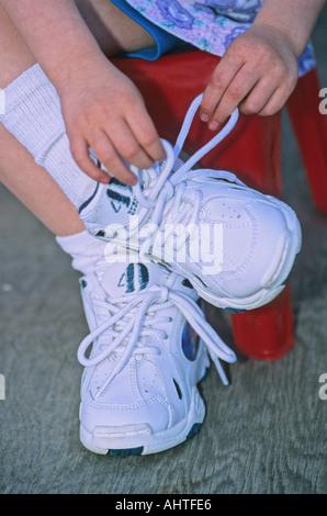 Eine Nahaufnahme eines jungen Menschen lernen, ihre Schuhe zu binden. - Stockfoto