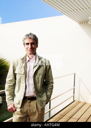 Mann steht auf Balkon, Lächeln, Porträt - Stockfoto
