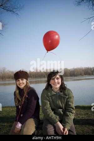 Junge (12-14) und Mädchen (10-12) Holding Ballon, Fluss, sitzt lächelnd - Stockfoto