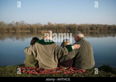Großeltern, Enkel (12-14) und Enkelin (10-12) sitzen Fluss, Rückansicht - Stockfoto
