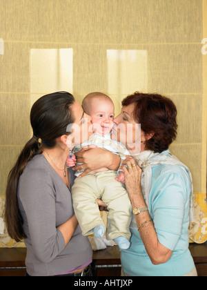 Mutter und Großmutter küssen Baby Boy (1-3 Monate) - Stockfoto
