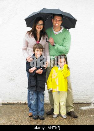 Eltern, jungen (6-8) und Mädchen (4-6) unter Dach, bergende lächelnd - Stockfoto