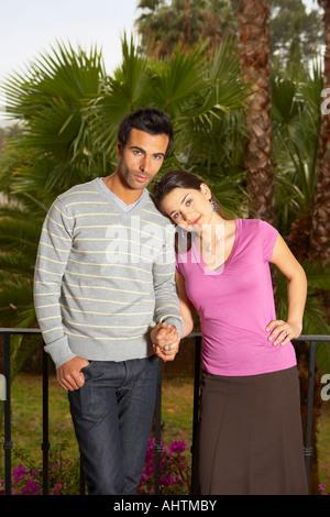Junges Paar Hand in Hand stehen auf Balkon, Lächeln, Porträt - Stockfoto