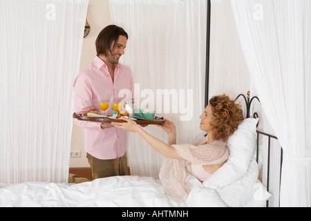 junger Mann lächelnd vorbei Frühstück Tablett Frau im Bett - Stockfoto