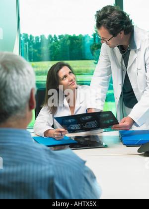 Zwei Ärzte Röntgen mit mündige Patient zu diskutieren. - Stockfoto