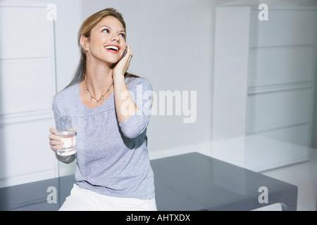 Frau auf Computertisch auf Handy. - Stockfoto