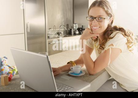 Junge Geschäftsfrau aus Küche zu Hause arbeiten. - Stockfoto