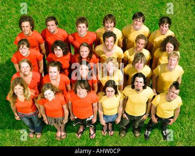 Gruppe auf Rasen stehen die Hälfte tragen orange Hälfte gelb - Stockfoto