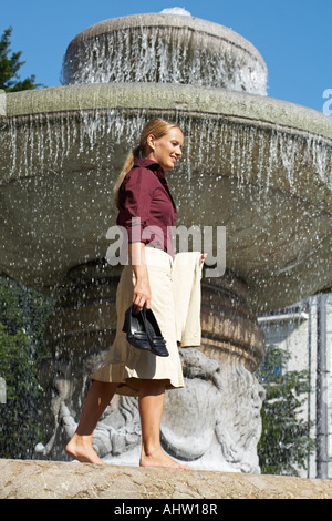 Geschäftsfrau laufen barfuß auf Brunnen Lachen Ansicht von unten. - Stockfoto
