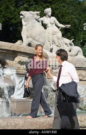 Lächelnde paar neben Brunnen Hand in Hand. - Stockfoto