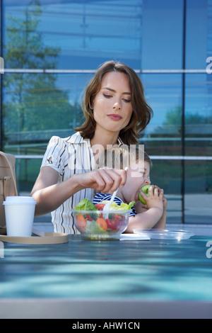 Geschäftsfrau und ihr Sohn am Tisch vor Büro außerhalb sie isst Salat zu ihrem Sohn zu essen Apfel gehen. - Stockfoto