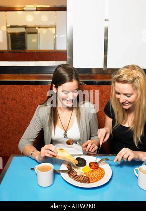 Zwei junge Frauen, die gemeinsame Mahlzeit in einem diner - Stockfoto