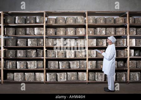 Käse-Arbeiter mit Zwischenablage, Rack mit Käse blickte. - Stockfoto