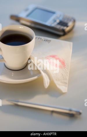 Lippenstift auf Serviette neben Kaffee - Stockfoto