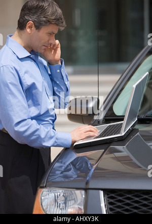 Geschäftsmann mit Laptop im Auto - Stockfoto