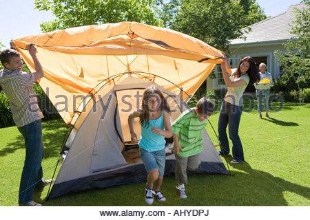 Familie Montage orange Kuppelzelt auf Wiese im Garten Großmutter servieren von Getränken im Hintergrund lächelt - Stockfoto