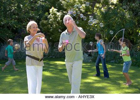 Kinder 8-13 Spiele mit Ball auf der Wiese im Garten Großeltern Seifenblasen in Luft mit Blase Wand im Vordergrund - Stockfoto