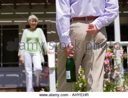 Ältere Frau absteigenden Veranda Schritte senior Mann tragenden Sektgläser und Flasche hinter Rücken im Garten im - Stockfoto