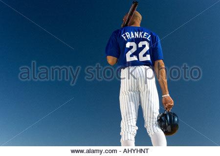 Baseball-Spieler gegen strahlend blauen Himmel, tragen Fledermaus auf Schulter, Rückansicht, niedrigen Winkel Ansicht - Stockfoto