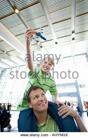 Vater mit Sohn auf Schultern in Flughafen, junge hält Spielzeug Flugzeug, smiling, niedrigen Winkel Ansicht - Stockfoto