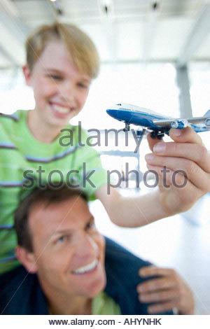 Vater mit Sohn auf Schultern in Flughafen, Junge Spielzeug Flugzeug hält lächelnd differenzielle Fokus - Stockfoto