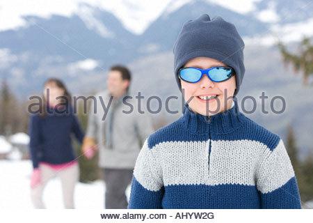 Jungen tragen wollene Mütze und Sonnenbrille im Schnee, Lächeln, Porträt, Eltern im Hintergrund - Stockfoto