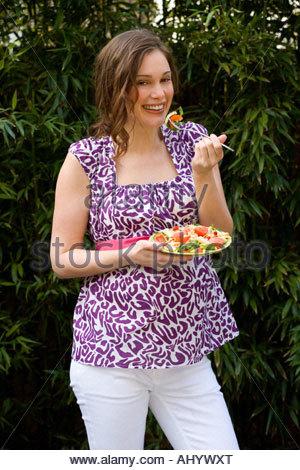 Schwangeren Frauen essen Salat im Freien, Lächeln, Porträt - Stockfoto