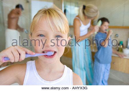 Mädchen, die ihre Zähneputzen im Bad, Portrait, Familie im Hintergrund - Stockfoto