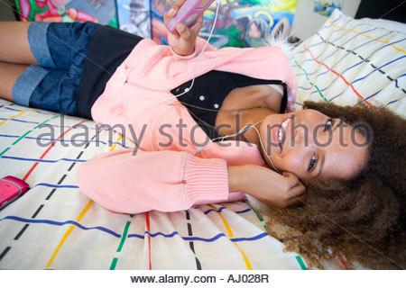 Teenager-Mädchen auf Bett trägt Kopfhörer und hält MP3-Player, Lächeln, Porträt, Nahaufnahme - Stockfoto