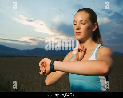 Frau in athletischer Gang Puls überprüfen - Stockfoto