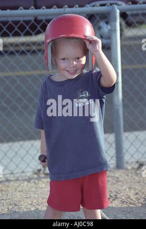 Ein Lächeln auf den Lippen kleiner Junge hebt einem Wimper Helm mehrere Größen zu groß Weg von seinen Augen als - Stockfoto