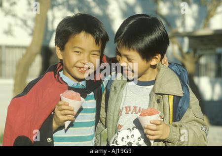 Zwei chinesische amerikanische Jungen Essen Snowcones in Chinatown Los Angeles CA - Stockfoto