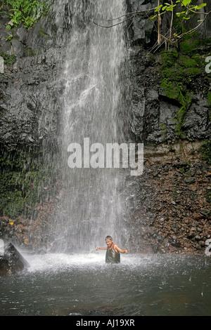 Einheimische junge spielt im kaskadierenden Spray von Sipyen Wasserfall in Kosrae Föderierte Staaten von Mikronesien - Stockfoto
