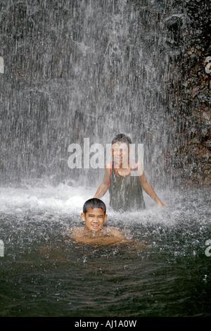 Einheimischen jungen spielen in cascading Spray von Sipyen Wasserfall in Kosrae Föderierte Staaten von Mikronesien - Stockfoto