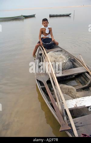 Ein Sohn wartet darauf, dass sein Vater an einem Angeltag aus ihrer ausgegraben Kanu auf dem Rio Tarajos - Stockfoto