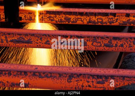 USA-Washington-Seattle-Funken fliegen von Acetylen Fackel schneiden Bars des roten heißen Stahl in Birmingham Stahlwerk - Stockfoto