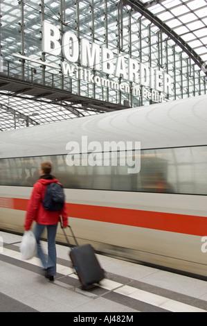 Ein Passagier mit Koffer zu Fuß wie eine verschwommene inter City express-Zug zieht in Berlin Hauptbahnhof. - Stockfoto