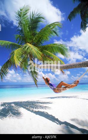 Frau in Hängematte unter Palme zwischen weißen Wolken und weißen Sandstränden in tropische Ferien - Stockfoto